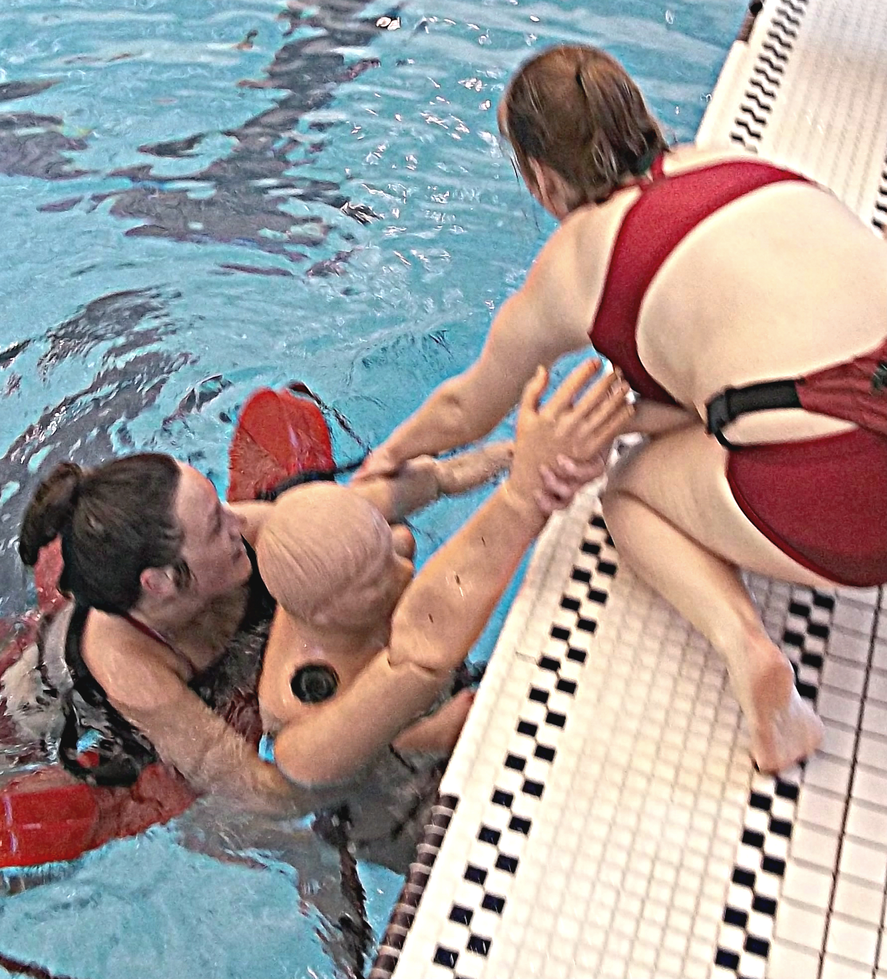 Two lifeguards demonstrating how to save a drowning victim