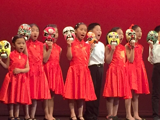Kids on a stage dressed in red